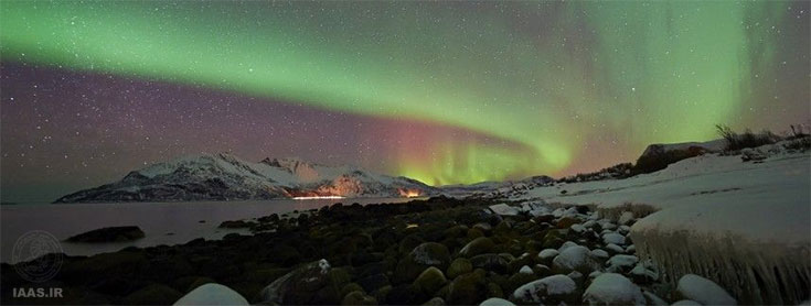 بازتاب شکل خط ساحلی یخزده در نور گسترده شفق قطبی از مایک کاری