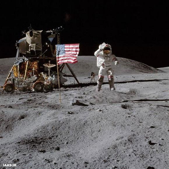 جان یانگ- در حال گام برداشتن- به پرچم ایالات متحده سلام میدهد. اعتبار عکس: ناسا